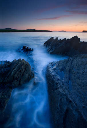 water breaking around rocks long exposure Stock Photo