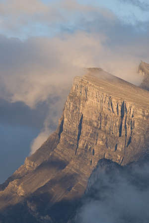 mount rundle in banff national park appearing out of clouds photo