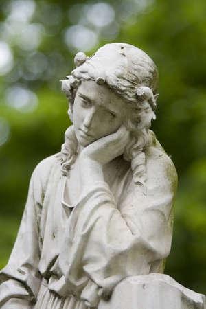 sad statue on cemetery