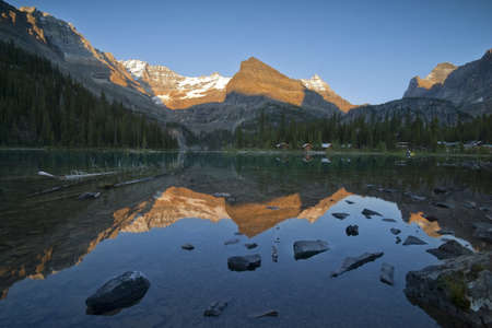 mountain tops around lake ohara glowing in sunset light, reflection in lake and tourist cabins on lakeshore