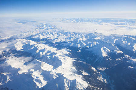aerial photo of alps, blue sky, mountain ranges and valleys, snow, winter Stock Photo