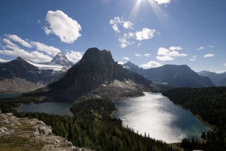assiniboine: mount assiniboine provincial park at midday taken from lookout, sunshine reflecting in lake,blue sky with some clouds Stock Photo