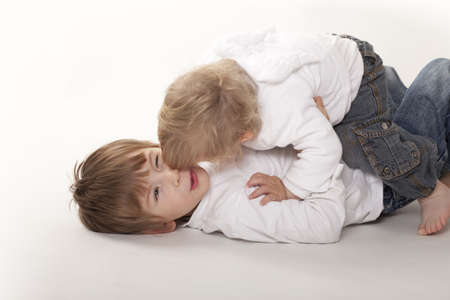 two boys embracing, lying on floor,white background Stock Photo