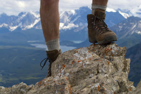 hiking symbol, closeup of boots on mountain top, kananskis range in background Stock Photo