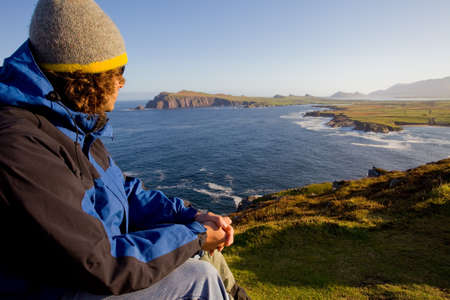 man relaxed sitting at coast on cliffs at dingle peninsula, enjoying ocean view
