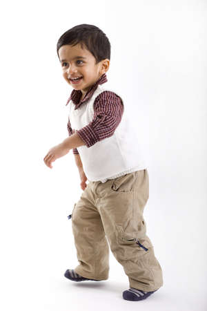 indian toddler boy standing having fun, white studio