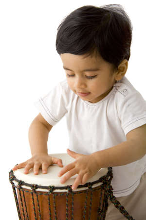 indian toddler boy drumming,white, studio