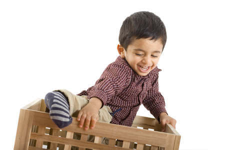 boy two years old climbing out of box, white background photo