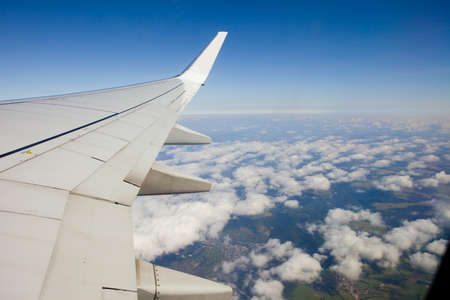 airfoil: airborne plain, airfoil and clouds with ground below Stock Photo