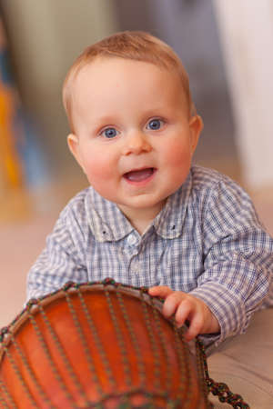 baby with drum looking to camera