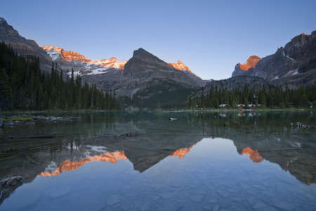 alpenglow: mountain tops around lake ohara glowing in sunset light, reflection in lake and tourist cabins on lakeshore Stock Photo