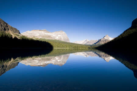 moutnain range illuminated by mornign light reflecting in lake ohara, tourist destination in canadian rocky mountains