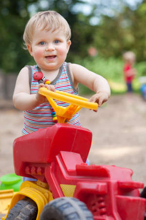 happy boy playing with truck outdoors in summer photo