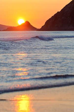 blasket islands: orange sunset on beach with waves rolling in and blasket islands in background, ireland Stock Photo