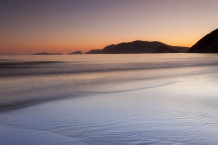 blasket islands: tranquil beach after sunset with islands,dingle,ireland Stock Photo