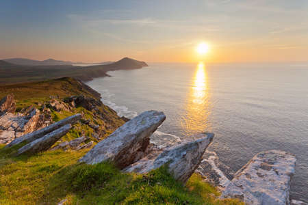 ocean view from high cliffs overlooking dingle coastline with setting sun