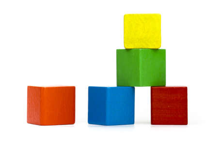 pyramid of colorful toy cubes and one single cube without function next to it on white background photo