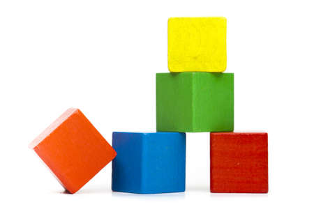 pyramid of colorful toy cubes and one single tilted cube without function next to it on white background