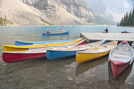 canoes on moraine lake with rocky mountains in background