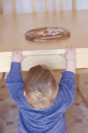 hungry kid reaching for bread on table, seen from behind