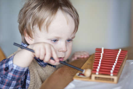 boy playing xylophone in house, concentrated look