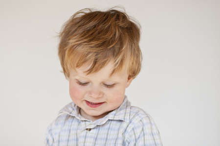 coy: coy boy with smile, 1 year old, head closeup in front of white wall