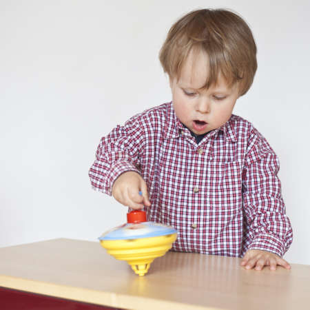 boy playing with spinner in home,watching concentrated Stock Photo - 13528228