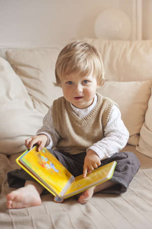child studying childrens book sitting on couch, 1 year old boy photo