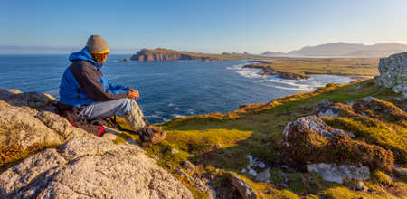 Man looking out on the coastline on a clear early morning, location  dingle peninsula in co Kerry, Western Ireland,Waymont near Graigue.