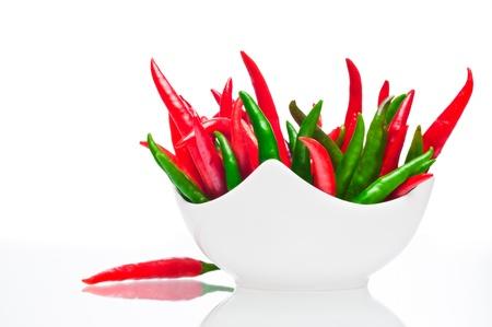 Rode en groene pepers in een kom op een witte achtergrond