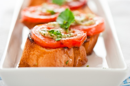 Bruschetta - gold baked baguette with tomato garlic and basil as appetizer photo