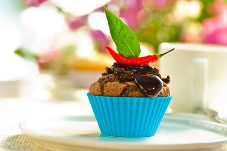 Hot chocolate cupcake with liquid chocolate and a red chili as a outdoor shooting photo