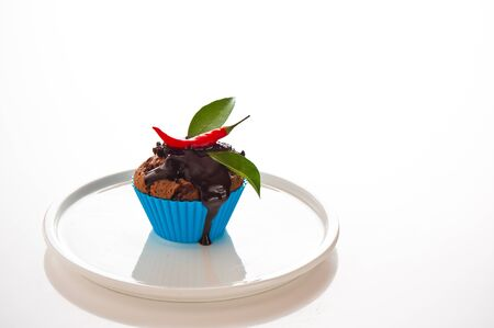 Hot chocolate cupcake with liquid chocolate and a red chili as a studio shooting photo