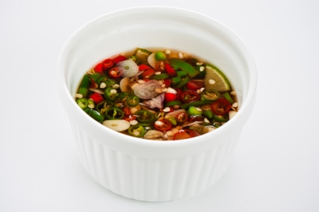 Hot spice chili fish sauce in a ramecin on white background photo