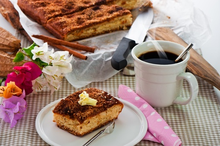 case sheet: A sheet cake with cinnamon sugar butter and a hot cup of coffee
