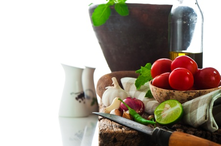 fresh vegetables and olive oil on an old weathered wood with a old mortar in behind over white background Stock Photo - 11765851