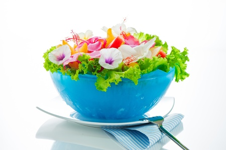 Fruit salad with edible flowers in a blue bowl from ice on white background photo
