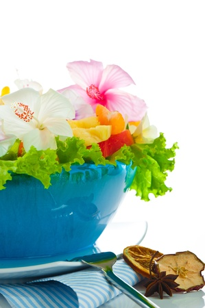 Fruit salad with edible flowers in a blue bowl from ice on white background Stock Photo - 11765857