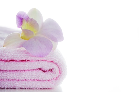 A pink towels with a orchid flower on white background and area for your text photo
