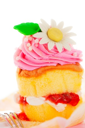 A two layer cupcake with pink and white buttercream sugar flower and gold powder on a white background as a studio shoot photo