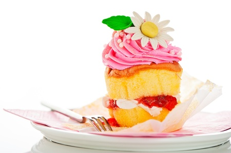 an icing: A two layer cupcake with pink and white buttercream sugar flower and gold powder on a white background as a studio shoot