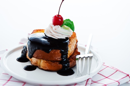 French toast with dark chocolate, white cream, red cherry and a leaf mint on a white background photo
