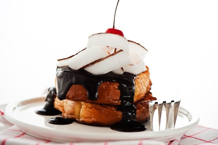French toast with dark chocolate, white cream, red cherry, coconut and a leaf mint on a white background photo