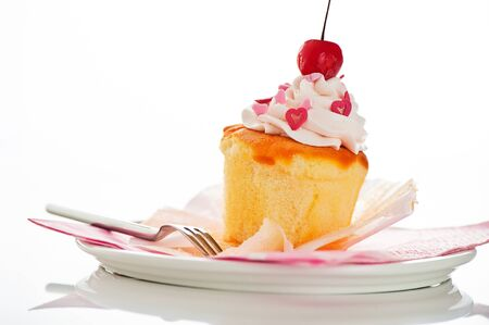 Vanilla cupcake with white cream heart as decoration and a cherry on the top on a white background as a studio shoot photo