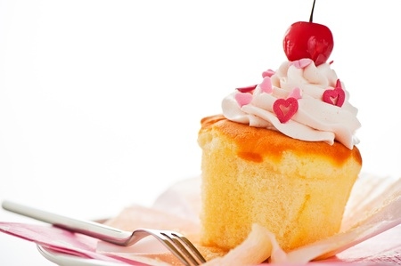 cupcakes isolated: Vanilla cupcake with white cream heart as decoration and a cherry on the top on a white background as a studio shoot Stock Photo