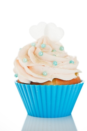 A cupcake in a blue baking cups with white cream, blue decoration and two hearts on the top on white background as a studio shoot Stock Photo - 12601527
