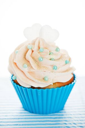 A cupcake in a blue baking cups with white cream, blue decoration and two hearts on the top on white background as a studio shoot Stock Photo - 12601536