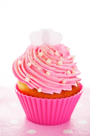 A cupcake in a pink baking cups with pink cream, white decoration and two hearts on the top on white background as a studio shoot photo
