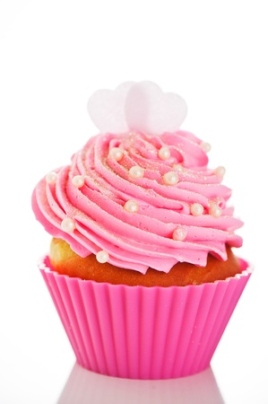 cupcakes isolated: A cupcake in a pink baking cups with pink cream, white decoration and two hearts on the top on white background as a studio shoot