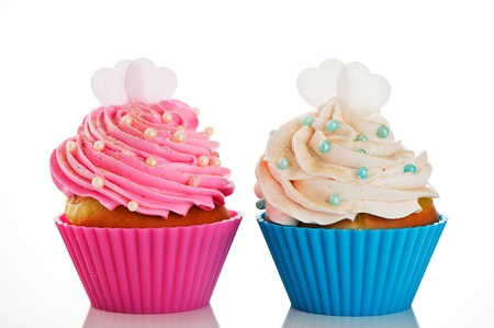 Two cupcakes in a pink and blue baking cups with pink and white cream, with decoration and two heart on the top on white background as a studio shoot photo